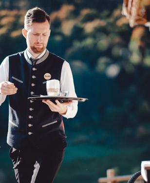 Kellner serviert einen Kaffe